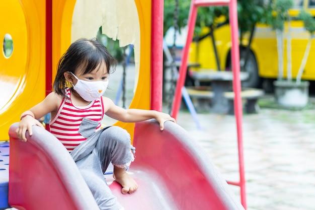 Gelukkig aziatisch kindmeisje die en stoffenmasker glimlachen dragen, zij die met schuifbalkstuk speelgoed spelen bij de speelplaats,
