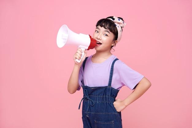 Gelukkig aziatisch kindmeisje die in megafoon schreeuwen die aankondiging maken in geïsoleerd op roze achtergrond.