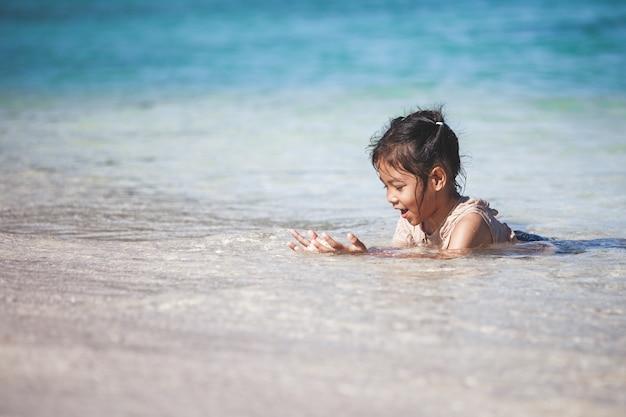 Gelukkig aziatisch kindmeisje die pret hebben om water in het mooie overzees in de zomervakantie te spelen
