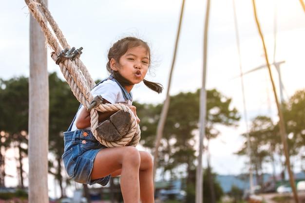Gelukkig aziatisch kindmeisje die pret op houten schommeling in speelplaats met mooie aard hebben te spelen