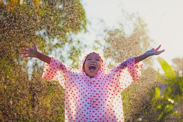 Gelukkig aziatisch kindmeisje die regenjas dragen die pret hebben om met de regen in het zonlicht te spelen