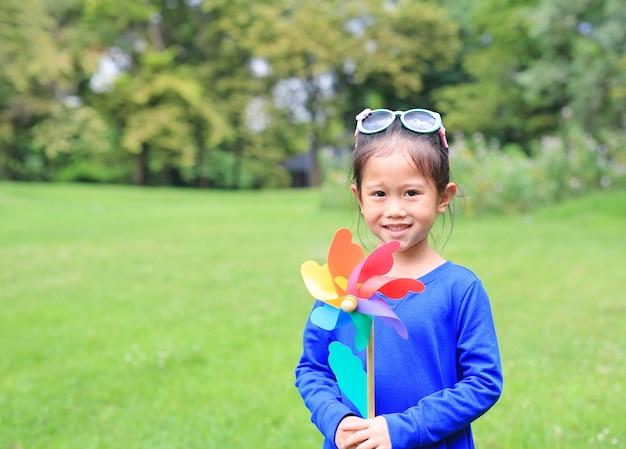 Gelukkig aziatisch kindmeisje met windturbine in de tuin