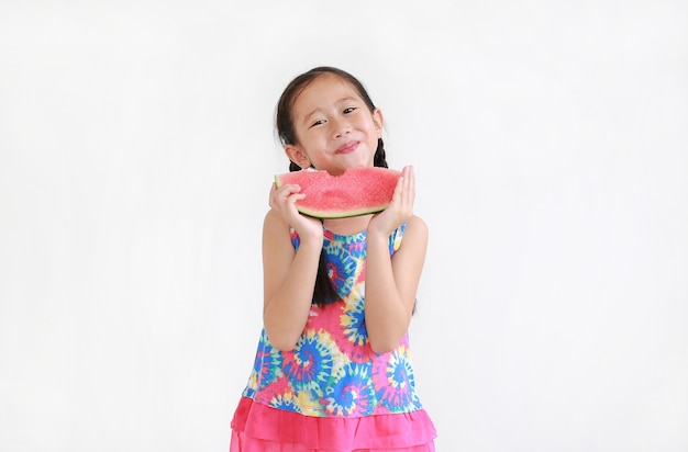 Gelukkig aziatisch klein kindmeisje dat watermeloen eet dat op wit wordt geïsoleerd