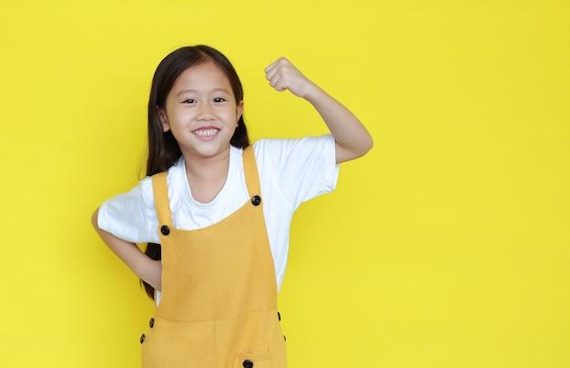 Gelukkig aziatisch klein kindmeisje die zijn spier met camera tonen die op gele achtergrond met exemplaarruimte wordt geïsoleerd.