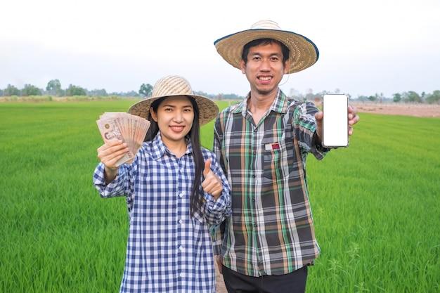 Gelukkig aziatisch landbouwerspaar die thais bankbiljet en smartphone met het lege scherm houden die zich bij rijstlandbouwbedrijf bevinden