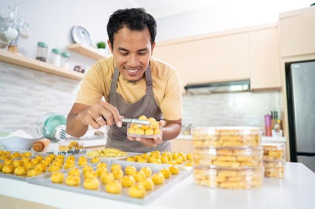 Gelukkig aziatisch mannelijk zelfgemaakte cake portret van jonge man zet nastar cake op een plastic containerdoos
