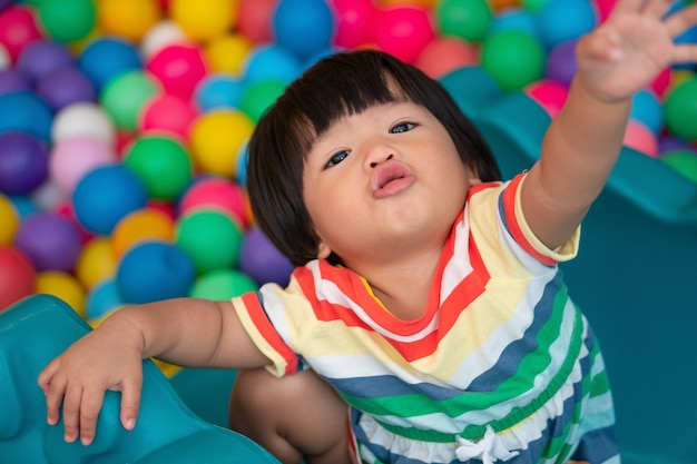 Gelukkig aziatisch meisje (anderhalf jaar oud) die kleine kleurrijke ballen in poolbal spelen. het spelen is het beste leren voor kinderen.