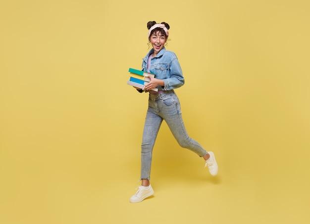 Gelukkig aziatisch meisje dat boek vasthoudt en over gele achtergrond springt. terug naar schoolconcept.