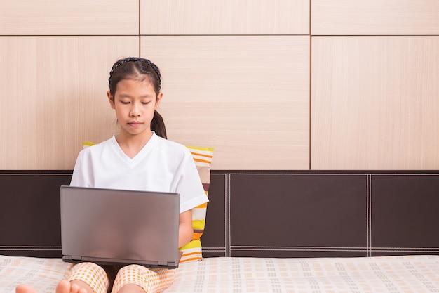 Gelukkig aziatisch meisje dat computerlaptop notitieboekje met behulp van