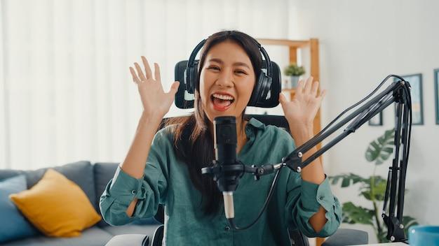 Gelukkig aziatisch meisje dat een podcast met hoofdtelefoons en microfoon opneemt