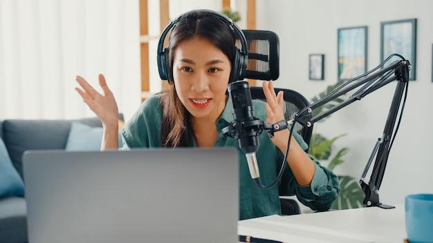 Gelukkig aziatisch meisje dat een podcast op haar laptopcomputer met hoofdtelefoons en microfoon opneemt
