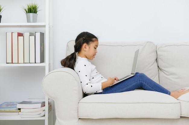Gelukkig aziatisch meisje dat laptop computer met behulp van