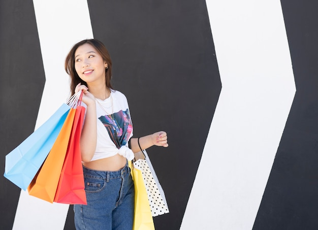 Gelukkig aziatisch meisje dat met kleurrijke zakken winkelt