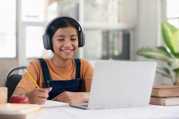 Gelukkig aziatisch meisje dat online thuis leert