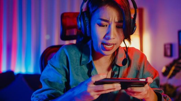 Gelukkig aziatisch meisje gamer met koptelefoon in competitie videogame online spelen met smartphone