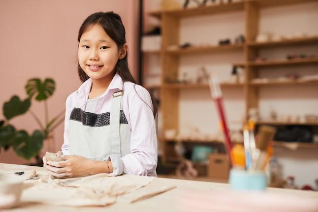 Gelukkig aziatisch meisje in aardewerk klasse
