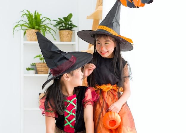 Gelukkig aziatisch meisje in heksenkostuum op halloween-viering.