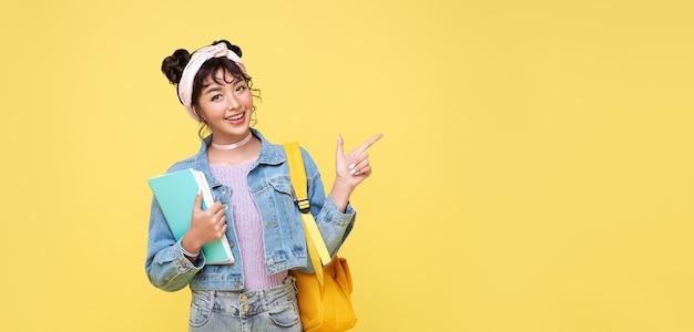 Gelukkig aziatisch meisje met de boeken van de rugzakholding en wijzende vinger op lege ruimte naast over gele achtergrond. terug naar school concept.