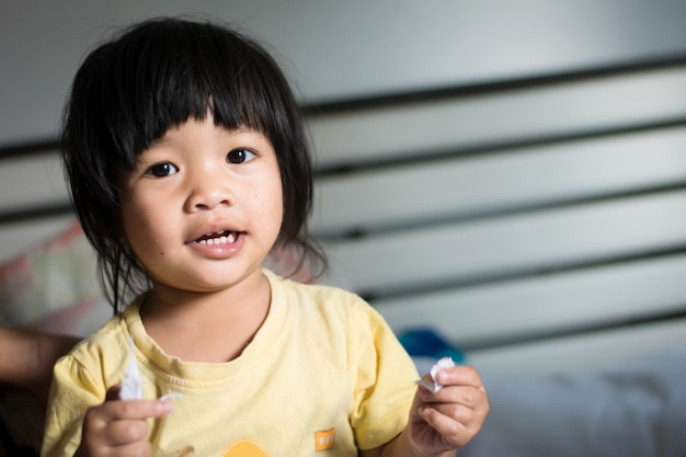 Gelukkig aziatisch meisje op het bed