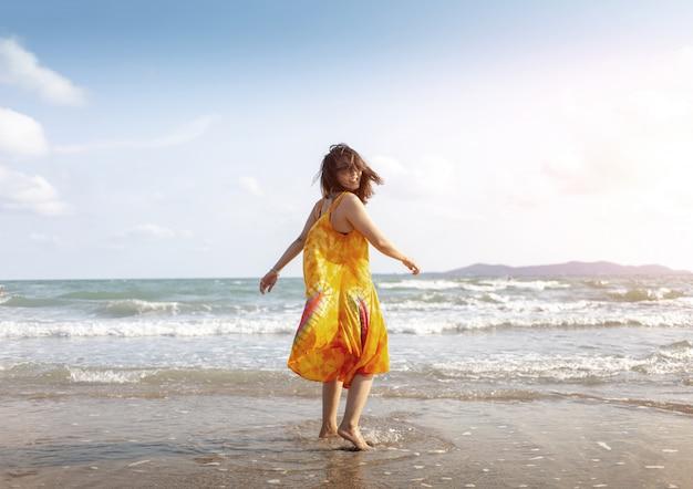 Gelukkig aziatisch meisje op oceaanstrand in roeping