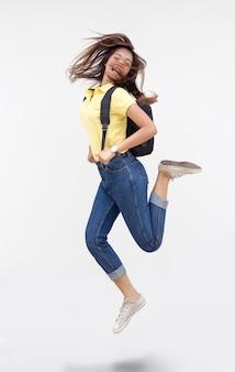 Gelukkig aziatisch meisje springen actie met schooltas op witte geïsoleerde achtergrond