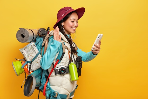 Gelukkig aziatisch meisje zwaait met palm, begroet iemand via videogesprek, houdt mobiele telefoon in de hand, draagt rugzak met alle noodzakelijke dingen, heeft wandeltocht, geïsoleerd over gele muur