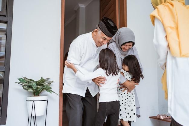 Gelukkig aziatisch moslim oud paar dat kinderen en kleinkinderen voor de deur ontmoet tijdens de viering van eid mubarak