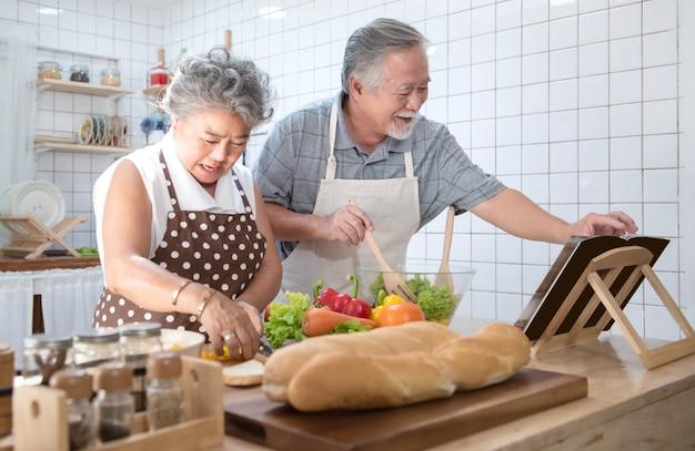 Gelukkig aziatisch ouder hoger paar die verse maaltijd in keuken thuis koken.