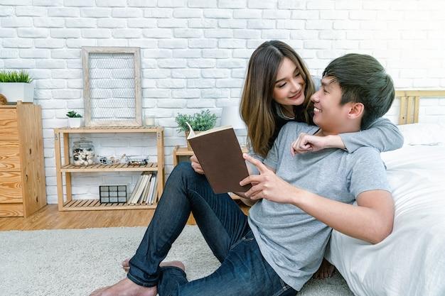 Gelukkig aziatisch paar dat het boek of het notitieboekje op het bed leest