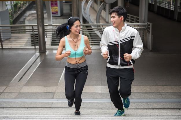 Gelukkig aziatisch paar dat in stedelijke stad in werking wordt gesteld