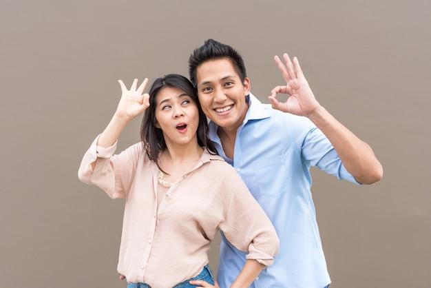 Gelukkig aziatisch paar dat met ok gebaar glimlacht