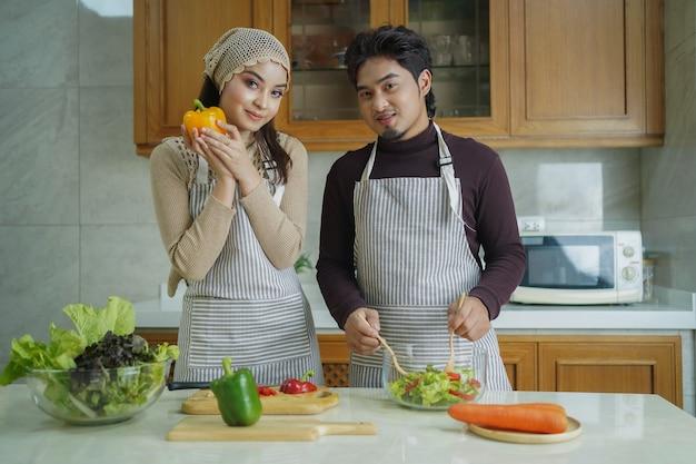 Gelukkig aziatisch paar dat samen kookt. echtgenoot en vrouw die in hun keuken thuis gezond plantaardig voedsel bereiden.