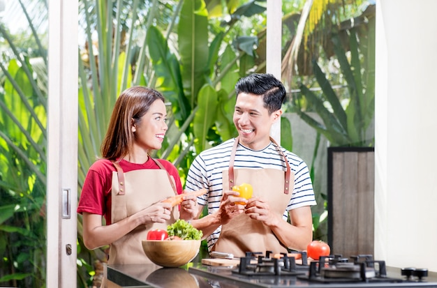Gelukkig aziatisch paar dat verse groenten voorbereidt voor het koken