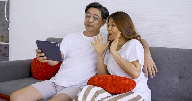 Gelukkig aziatisch paar die foto's samen in woonkamer nemen.