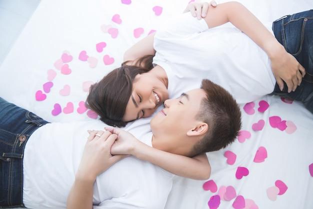 Gelukkig aziatisch paar op het bed thuis