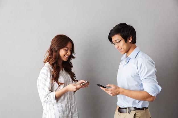 Gelukkig aziatisch paar status geïsoleerd, met behulp van mobiele telefoons