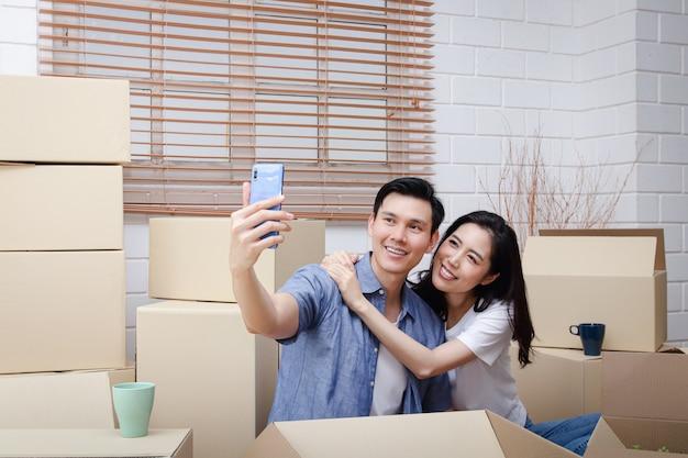 Gelukkig aziatisch paar verhuizen naar een nieuw huis neem een smartphone en maak een selfie. concept van het starten van een nieuw leven bouw een gezin. kopieer ruimte