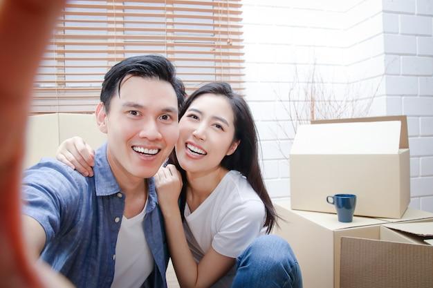 Gelukkig aziatisch paar verhuizen naar een nieuw huis neem een smartphone en maak een selfie. concept van het starten van een nieuw leven bouw een gezin.