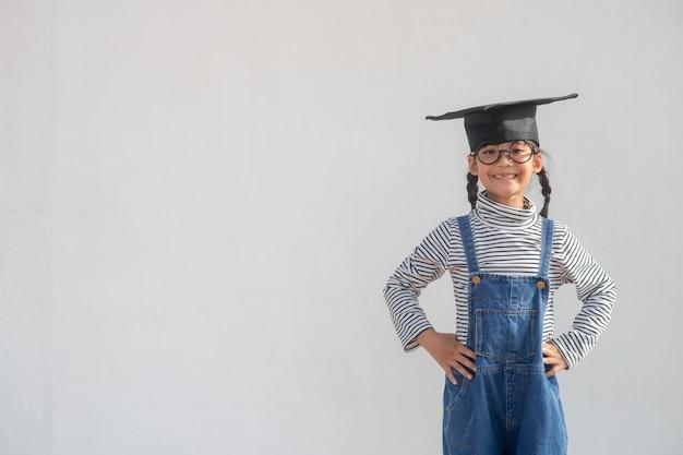 Gelukkig aziatisch schoolkind afgestudeerd in afstudeerpet