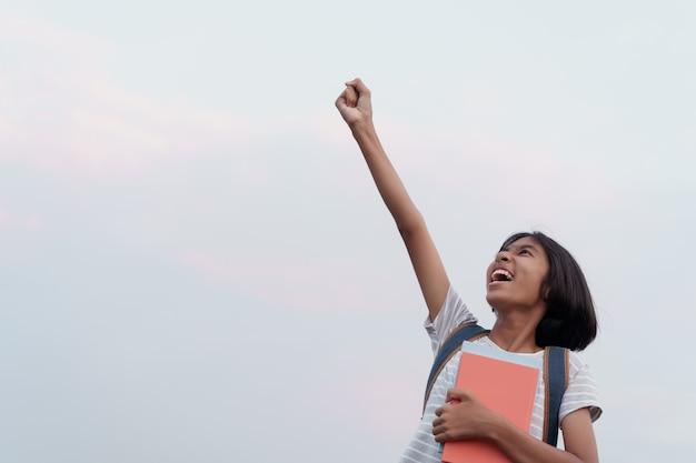Gelukkig aziatisch schoolmeisjessucces en opgewekt op het gezicht terwijl het houden van een boek met hand aan blauwe hemel wordt opgeheven