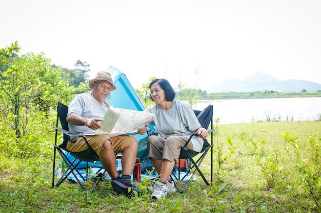 Gelukkig aziatisch senior koppel kamperen aan de waterkant, zittend op een stoel, toeristische kaart bekijken, met kopieerruimte.