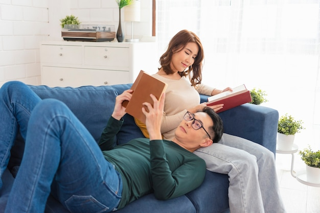 Gelukkig aziatisch stel brengt het weekend samen door op de bank binnenshuis, ontspannend en genietend van het lezen van een boek.