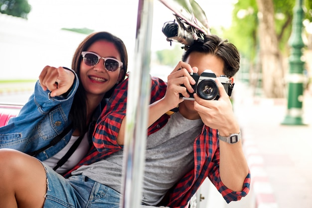 Gelukkig aziatisch toeristenpaar die op tuk tuk-taxi in bangkok thailand reizen