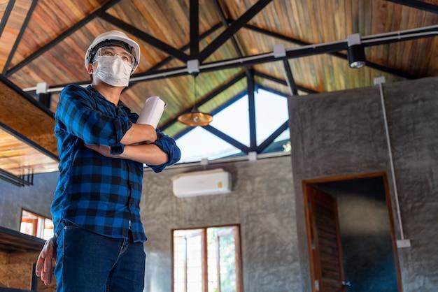 Gelukkig aziatische bouwingenieur technicus permanent met armen gekruist vol vertrouwen na het inspecteren van de houtstructuur onder het dak op de bouwplaats of bouwplaats van een huis.