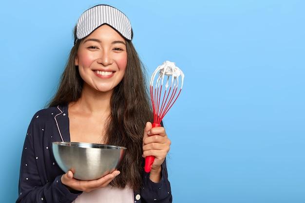 Gelukkig aziatische brunette vrouw maakt heerlijke cake, bereidt cake, gardes eiwit in kom met klopper, gekleed in nachtkleding, slaapmasker