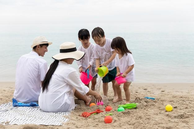 Gelukkig aziatische familie vijf mensen op zomervakantie spelen speelgoed op zand in het strand samen in de ochtend tijd, zonsopgang. vakantie en reizen concept.