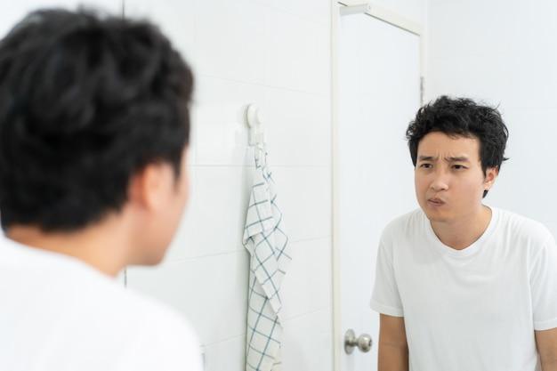 Gelukkig aziatische jongeman in wit t-shirt kijken naar zichzelf in de spiegel in toilet in de ochtend. een man die zijn gezicht en lichaam voorbereidt en controleert voordat hij aan het werk gaat. routinematige activiteit in het dagelijks leven.