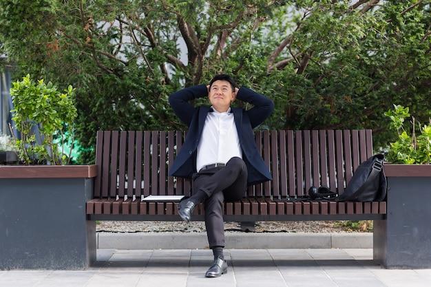 Gelukkig aziatische kantoormedewerker, zakenman zittend en rustend op een bankje in het stadspark buiten. zakelijke man werknemer een formeel pak pauze rust en ontspan van buitenaf. straat in het centrum, stedelijke achtergrond