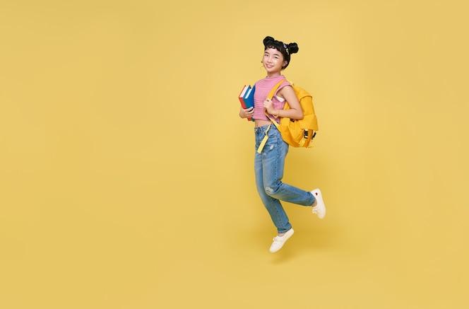 Gelukkig aziatische kind student springen met schooltasje en boek geïsoleerd op gele achtergrond.