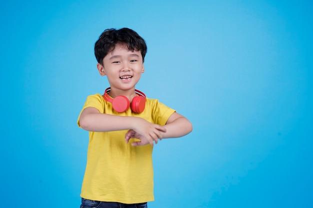 Gelukkig aziatische kleine jongen met koptelefoon luisteren naar muziek Premium Foto